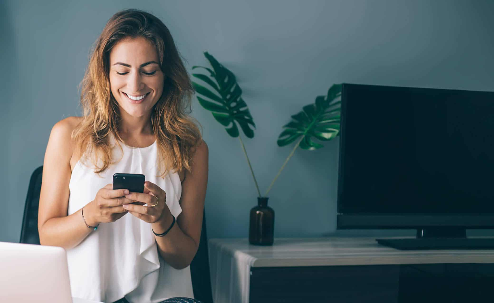 Woman smiling while using her iPhone at home