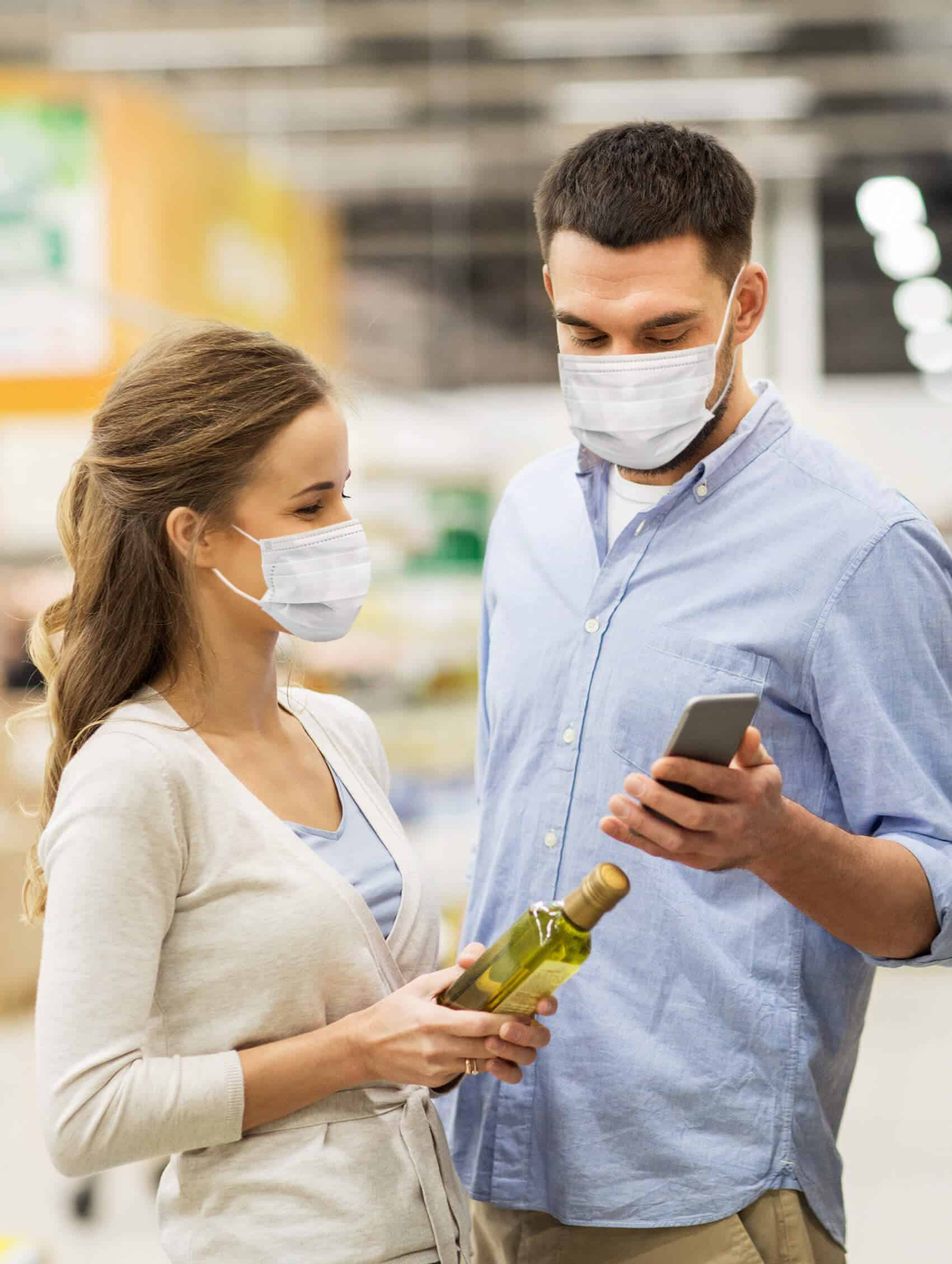 Man and woman grocery shopping while looking at a phone