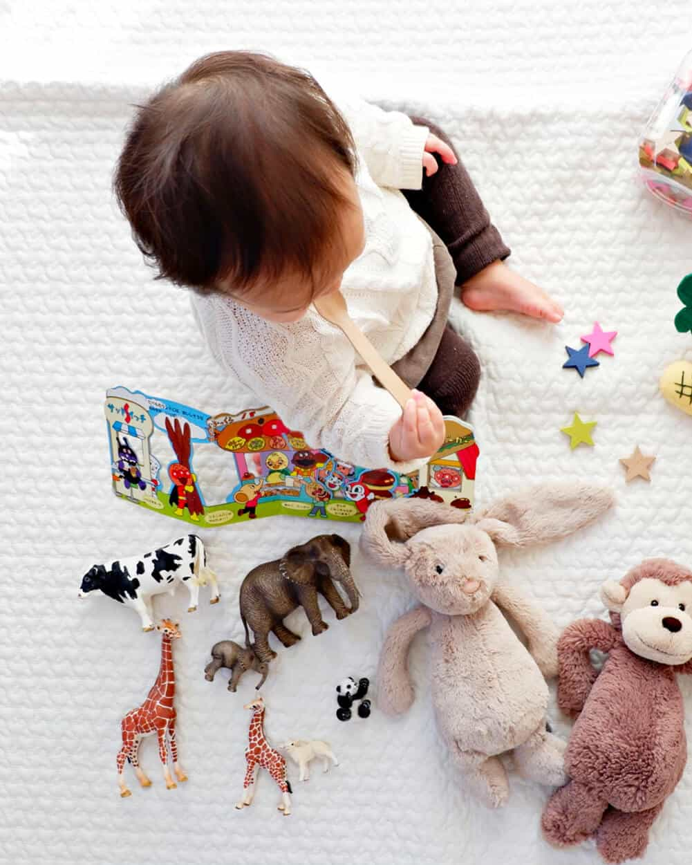 Infant sitting on a blanked playing with toys